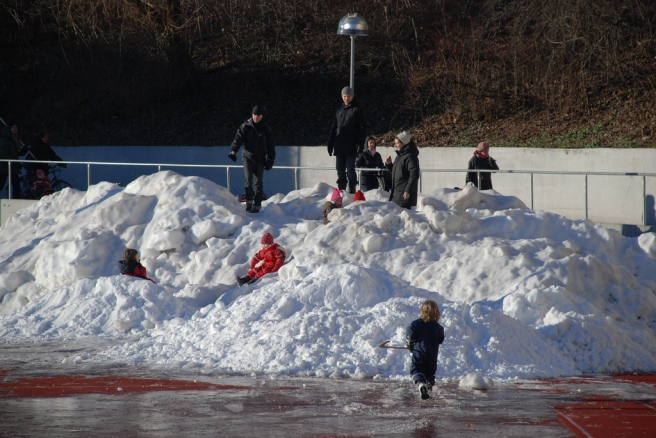 Kids play in piles of snow
